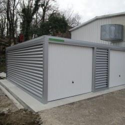 Siva garaža z belimi vrati za dva avtomobila