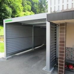 Garaža za avtomobil - enojna v sivi barvi postavljena ob hiši
