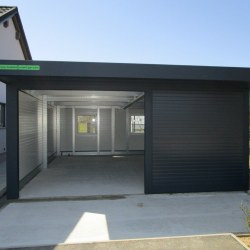 Široka garaža z nadstreškom nad vrati ob hiši