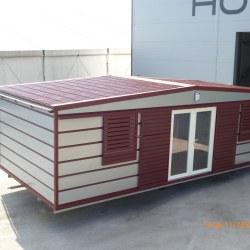 Hosekra mobilna hiška z okni spredaj in zunanjimi drsnimi žaluzijami.