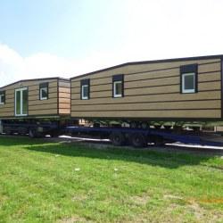 Mobilni hiški Hosekra Magnolija v imitaciji lesa, naloženi na kamion.