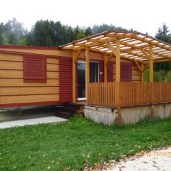 Mobilna hiška Hosekra v imitaciji lesa, postavljena na nivelirnih podstavkih.