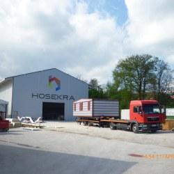 Hosekra mobilna hiška Magnolija s srebrno fasado, naložena na kamion.